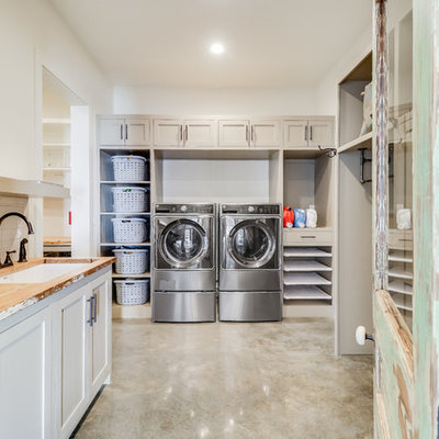Utility room - country u-shaped concrete floor and gray floor utility room idea in Jackson with an undermount sink, shaker cabinets, beige cabinets, wood countertops, white walls, a side-by-side washer/dryer and beige countertops