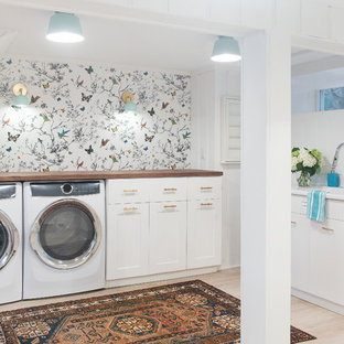 Design ideas for a mid-sized transitional utility room in Boston with an integrated sink, recessed-panel cabinets, white cabinets, wood benchtops, white walls, light hardwood floors, a side-by-side washer and dryer and beige floor.
