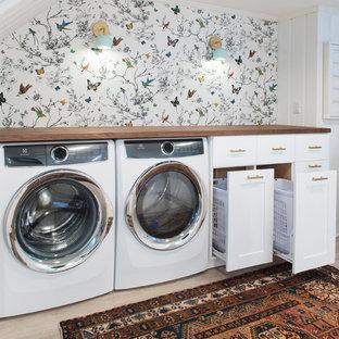 Idéer för ett mellanstort klassiskt grovkök, med luckor med infälld panel, vita skåp, träbänkskiva, vita väggar, ljust trägolv, en tvättmaskin och torktumlare bredvid varandra och beiget golv