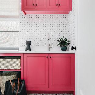 Immagine di una lavanderia tradizionale con lavello sottopiano, ante in stile shaker, ante rosse, pareti bianche, pavimento multicolore e top bianco