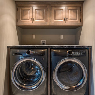 Inspiration for a small traditional single-wall separated utility room in Boston with raised-panel cabinets, medium wood cabinets, beige walls, ceramic flooring, a side by side washer and dryer, brown floors and black worktops.