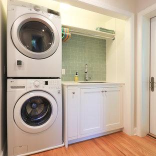 Idéer för små vintage linjära vitt tvättstugor enbart för tvätt, med en undermonterad diskho, luckor med infälld panel, vita skåp, bänkskiva i kvarts, beige väggar, ljust trägolv, en tvättpelare och brunt golv