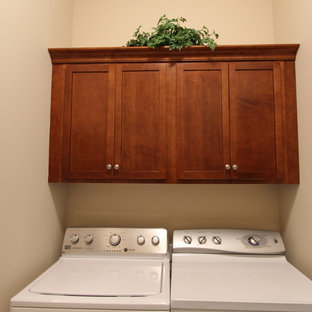 Small transitional single-wall laundry cupboard in Grand Rapids with recessed-panel cabinets, quartz benchtops, multi-coloured splashback, a drop-in sink, dark wood cabinets, beige walls, linoleum floors and a side-by-side washer and dryer.