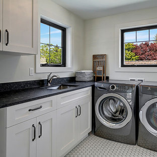 Inspiration for a traditional l-shaped separated utility room in Seattle with a submerged sink, shaker cabinets, white cabinets, white walls, a side by side washer and dryer, white floors and black worktops.