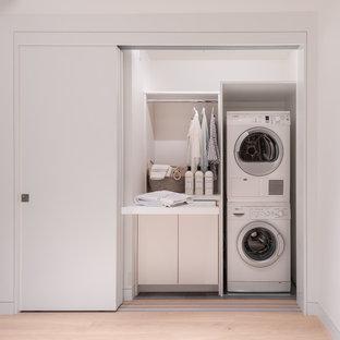 Ispirazione per un piccolo ripostiglio-lavanderia minimal con ante bianche, pareti bianche, lavatrice e asciugatrice a colonna, pavimento beige, top bianco, ante lisce e parquet chiaro