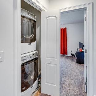 Ispirazione per un piccolo ripostiglio-lavanderia minimal con pareti grigie, moquette, lavatrice e asciugatrice a colonna e pavimento beige