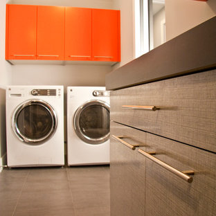 Bild på en liten funkis svarta linjär svart tvättstuga enbart för tvätt, med släta luckor, orange skåp, laminatbänkskiva och en tvättmaskin och torktumlare bredvid varandra
