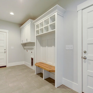 Photo of a large farmhouse galley utility room in Raleigh with shaker cabinets, white cabinets, grey walls, porcelain flooring, a side by side washer and dryer and grey floors.