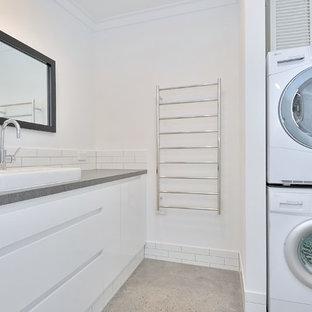 Esempio di una lavanderia multiuso moderna di medie dimensioni con ante lisce, ante bianche, top in cemento, pareti bianche, pavimento in cemento, lavatrice e asciugatrice a colonna, pavimento grigio e top grigio
