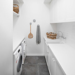 Inspiration for a transitional galley dedicated laundry room in Perth with a farmhouse sink, shaker cabinets, white cabinets, white walls, a side-by-side washer and dryer, grey floor and white benchtop.