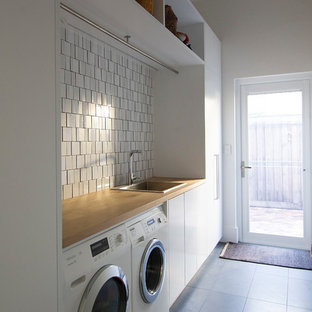 Contemporary single-wall dedicated laundry room in Perth with a drop-in sink, flat-panel cabinets, white cabinets, wood benchtops, white walls, slate floors, a side-by-side washer and dryer, grey floor and brown benchtop.