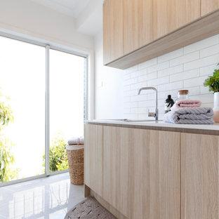 Bild på ett mellanstort vit parallellt vitt grovkök, med en undermonterad diskho, skåp i ljust trä, bänkskiva i kvarts, vita väggar, klinkergolv i keramik och vitt golv