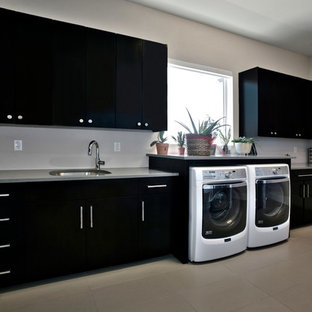Large contemporary l-shaped utility room in Dallas with a submerged sink, flat-panel cabinets, composite countertops, beige walls, ceramic flooring, a side by side washer and dryer and black cabinets.