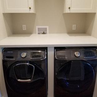 Esempio di un piccolo ripostiglio-lavanderia minimalista con ante in stile shaker, ante bianche, top in superficie solida, pareti beige, pavimento in legno massello medio, lavatrice e asciugatrice affiancate, pavimento marrone e top bianco