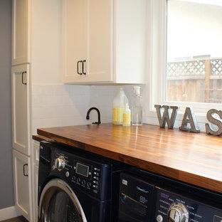 Inredning av ett amerikanskt litet grovkök, med en undermonterad diskho, skåp i shakerstil, vita skåp, träbänkskiva, grå väggar, klinkergolv i porslin och en tvättmaskin och torktumlare bredvid varandra