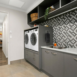 Inspiration for a contemporary single-wall dedicated laundry room in Other with a drop-in sink, flat-panel cabinets, grey cabinets, white walls, a side-by-side washer and dryer, beige floor and grey benchtop.