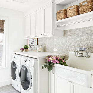 Example of a mid-sized transitional single-wall gray floor and porcelain tile dedicated laundry room design in San Francisco with an utility sink, shaker cabinets, white cabinets, white walls, a side-by-side washer/dryer, white countertops and quartzite countertops