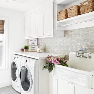 Modelo de cuarto de lavado lineal, tradicional renovado, de tamaño medio, con pila para lavar, armarios estilo shaker, puertas de armario blancas, paredes blancas, lavadora y secadora juntas, suelo gris, encimeras blancas, encimera de cuarcita y suelo de baldosas de porcelana