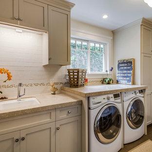 Esempio di una sala lavanderia tradizionale di medie dimensioni con lavello sottopiano, ante in stile shaker, ante grigie, pareti beige, lavatrice e asciugatrice affiancate, pavimento grigio e top beige