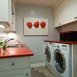 Klassisk inredning av en mellanstor röda parallell rött tvättstuga enbart för tvätt, med en nedsänkt diskho, skåp i shakerstil, vita skåp, bänkskiva i kvarts, grå väggar, klinkergolv i porslin och en tvättmaskin och torktumlare bredvid varandra