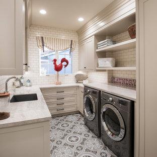 Immagine di una sala lavanderia chic con lavello sottopiano, ante a filo, ante beige, lavatrice e asciugatrice affiancate, pavimento multicolore e top beige
