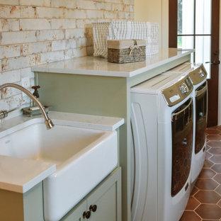 Exempel på en mellanstor lantlig vita linjär vitt tvättstuga enbart för tvätt, med en rustik diskho, skåp i shakerstil, gröna skåp, bänkskiva i kvarts, vita väggar, klinkergolv i terrakotta, en tvättmaskin och torktumlare bredvid varandra och brunt golv
