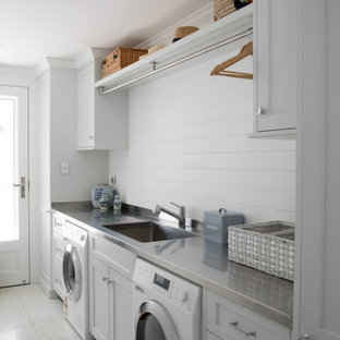Inspiration for a traditional single-wall laundry room in Brisbane with an undermount sink, shaker cabinets, white cabinets, white walls, grey floor and grey benchtop.
