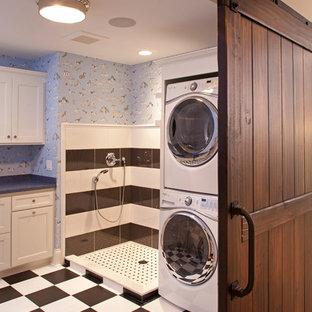 На фото: большая отдельная, угловая прачечная в классическом стиле с фасадами с утопленной филенкой, белыми фасадами, синими стенами, полом из керамической плитки и с сушильной машиной на стиральной машине с