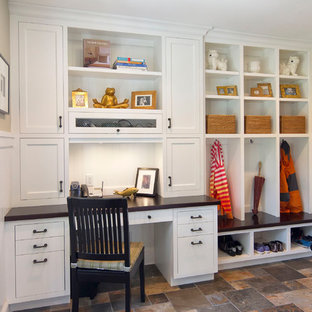 Example of a classic galley slate floor utility room design in New York with flat-panel cabinets, white cabinets, wood countertops, beige walls and black countertops
