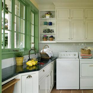 Idéer för vintage svart tvättstugor, med vita skåp och brunt golv