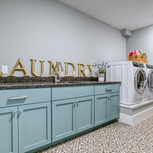 Example of a large transitional single-wall multicolored floor dedicated laundry room design in Other with an undermount sink, shaker cabinets, blue cabinets, gray walls, a side-by-side washer/dryer and gray countertops