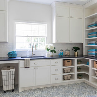 Laundry room - transitional l-shaped multicolored floor laundry room idea in Houston with an undermount sink, shaker cabinets, white cabinets, white walls and black countertops