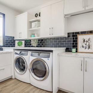 Inspiration för en funkis vita l-formad vitt tvättstuga enbart för tvätt, med en nedsänkt diskho, släta luckor, vita skåp, laminatbänkskiva, vita väggar, mellanmörkt trägolv, en tvättmaskin och torktumlare bredvid varandra och brunt golv