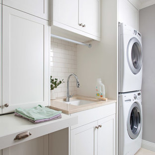 Inspiration for a timeless dedicated laundry room remodel in Austin with an undermount sink, shaker cabinets, white cabinets, gray walls and a stacked washer/dryer