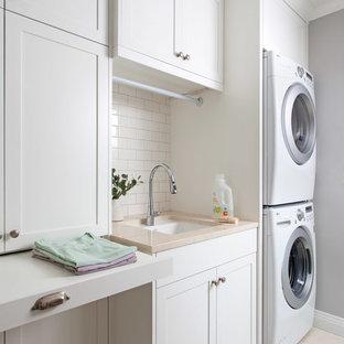 Exemple d'une buanderie chic dédiée avec un évier encastré, un placard à porte shaker, des portes de placard blanches, un mur gris et des machines superposées.