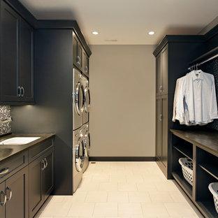 Immagine di una lavanderia classica con lavatrice e asciugatrice a colonna, pavimento beige e top grigio
