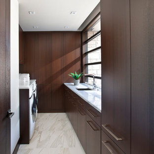 Trendy marble floor dedicated laundry room photo in Detroit with an undermount sink, flat-panel cabinets, dark wood cabinets, marble countertops and a side-by-side washer/dryer