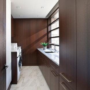 Idéer för funkis tvättstugor enbart för tvätt, med en undermonterad diskho, släta luckor, skåp i mörkt trä, marmorbänkskiva, marmorgolv och en tvättmaskin och torktumlare bredvid varandra
