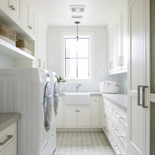 Beach style u-shaped white floor dedicated laundry room photo in Orange County with a farmhouse sink, recessed-panel cabinets, white cabinets, white walls, a side-by-side washer/dryer and gray countertops