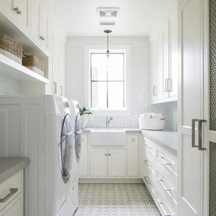 Inspiration för en maritim grå u-formad grått tvättstuga enbart för tvätt, med en rustik diskho, luckor med infälld panel, vita skåp, vita väggar, en tvättmaskin och torktumlare bredvid varandra och vitt golv