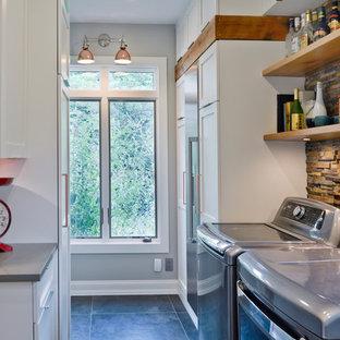 Foto de lavadero multiusos y de galera, bohemio, de tamaño medio, con armarios estilo shaker, puertas de armario blancas, encimera de cuarzo compacto, paredes grises, suelo de baldosas de porcelana, lavadora y secadora juntas y suelo gris