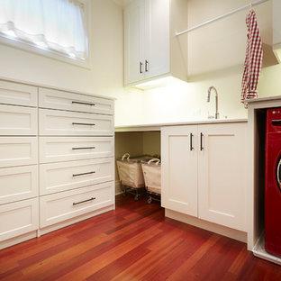Ispirazione per una lavanderia multiuso stile americano di medie dimensioni con lavello da incasso, ante in stile shaker, ante bianche, top in quarzo composito, pareti bianche, parquet scuro, lavatrice e asciugatrice affiancate, pavimento rosso e top bianco