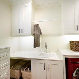 Foto di una lavanderia multiuso stile americano di medie dimensioni con lavello da incasso, ante in stile shaker, ante bianche, top in quarzo composito, pareti bianche, parquet scuro, lavatrice e asciugatrice affiancate, pavimento rosso e top bianco