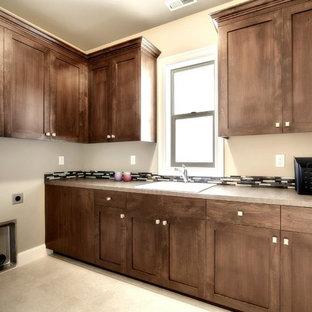 Ispirazione per una grande sala lavanderia stile americano con lavello da incasso, ante in stile shaker, ante in legno bruno, top in cemento, pareti beige, pavimento con piastrelle in ceramica, lavatrice e asciugatrice affiancate e pavimento beige