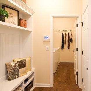 Idee per una piccola lavanderia multiuso american style con ante in legno chiaro, parquet scuro, pareti beige e lavatrice e asciugatrice affiancate