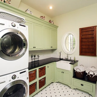 Traditional laundry room in Jacksonville with a farmhouse sink, green cabinets and a stacked washer and dryer.