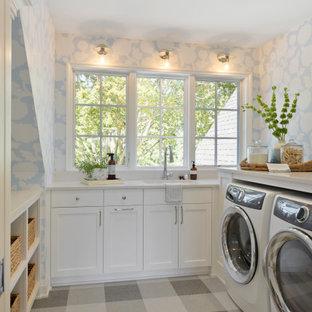Exempel på en maritim vita u-formad vitt tvättstuga enbart för tvätt, med en undermonterad diskho, skåp i shakerstil, vita skåp, blå väggar och grått golv