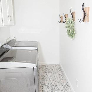 Idée de décoration pour une petit buanderie parallèle marine dédiée avec un évier de ferme, un mur blanc, un sol en carrelage de céramique, des machines côte à côte et un sol bleu.