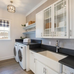 Design ideas for a medium sized country single-wall separated utility room in Jacksonville with a belfast sink, glass-front cabinets, white cabinets, granite worktops, white walls, medium hardwood flooring, a side by side washer and dryer, brown floors and black worktops.