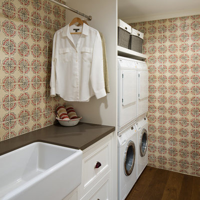 Example of a country galley dark wood floor dedicated laundry room design in San Diego with a farmhouse sink, multicolored walls, a stacked washer/dryer, white cabinets and recessed-panel cabinets